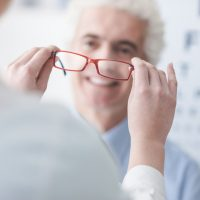 Optician giving new glasses to a male patient, he is smiling, eye chart on the background